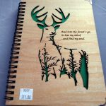 A wooden notebook with carved deer